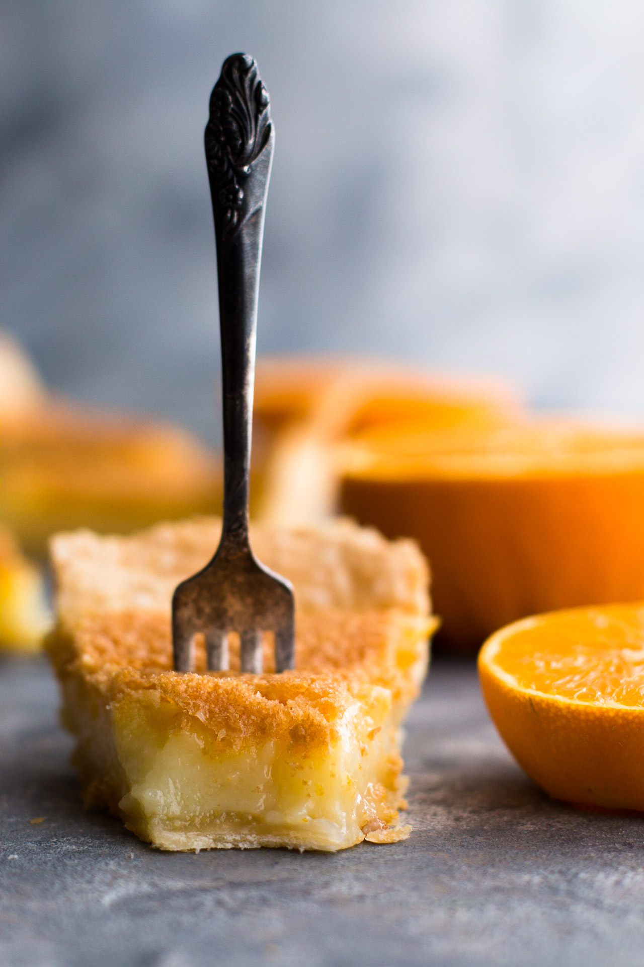 Vertical side shot of a pie with a bite taken out of it and a fork standing up vertically in it. Surrounded by orange halves.