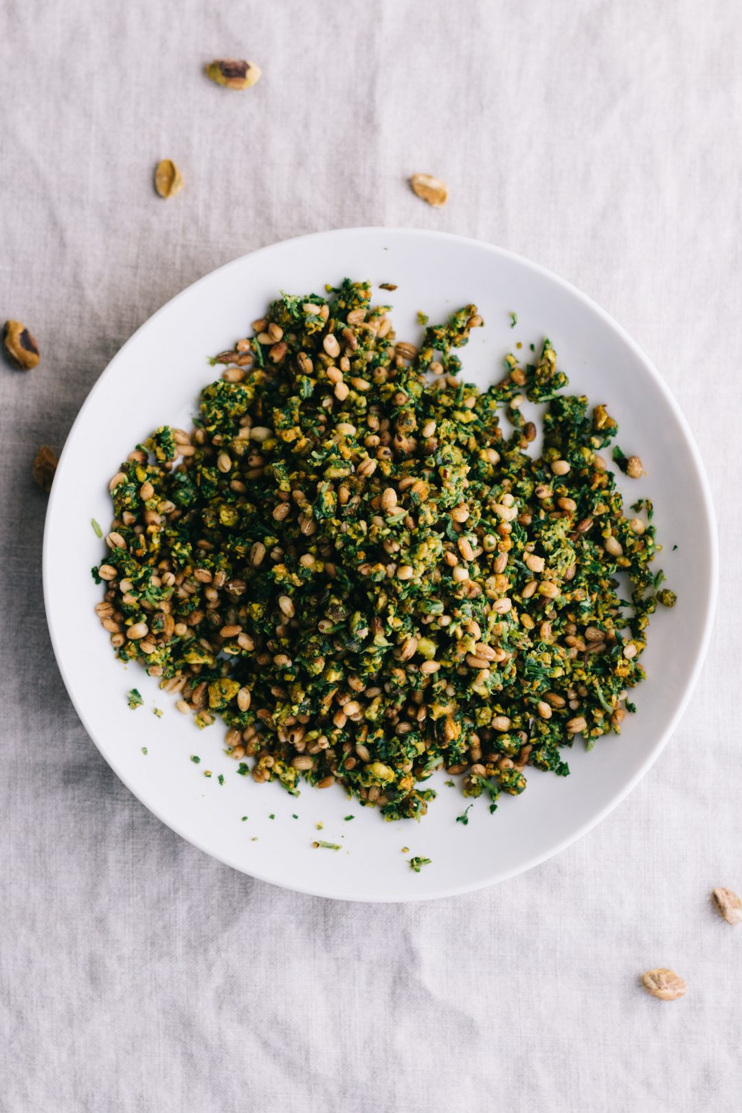 Overhead flatlay shot of pistachio gremolata with barley in a shallow bowl on a cloth covered surface.