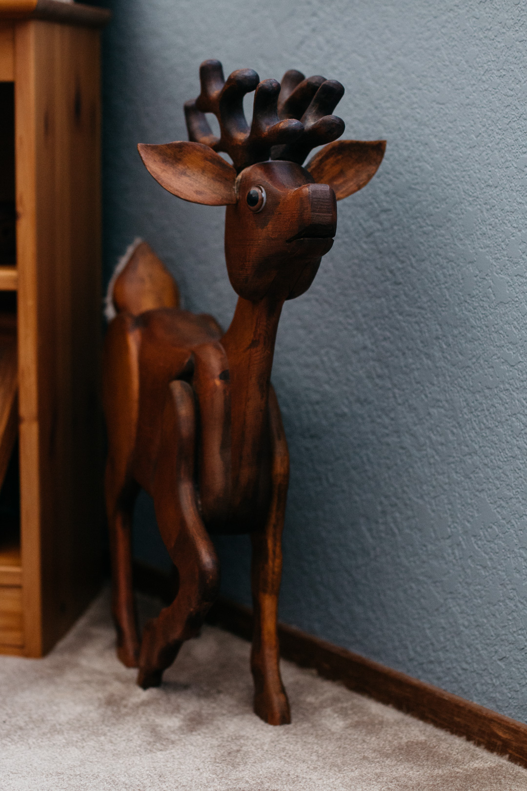 A vertical side angle shot of a wood crafted reindeer.
