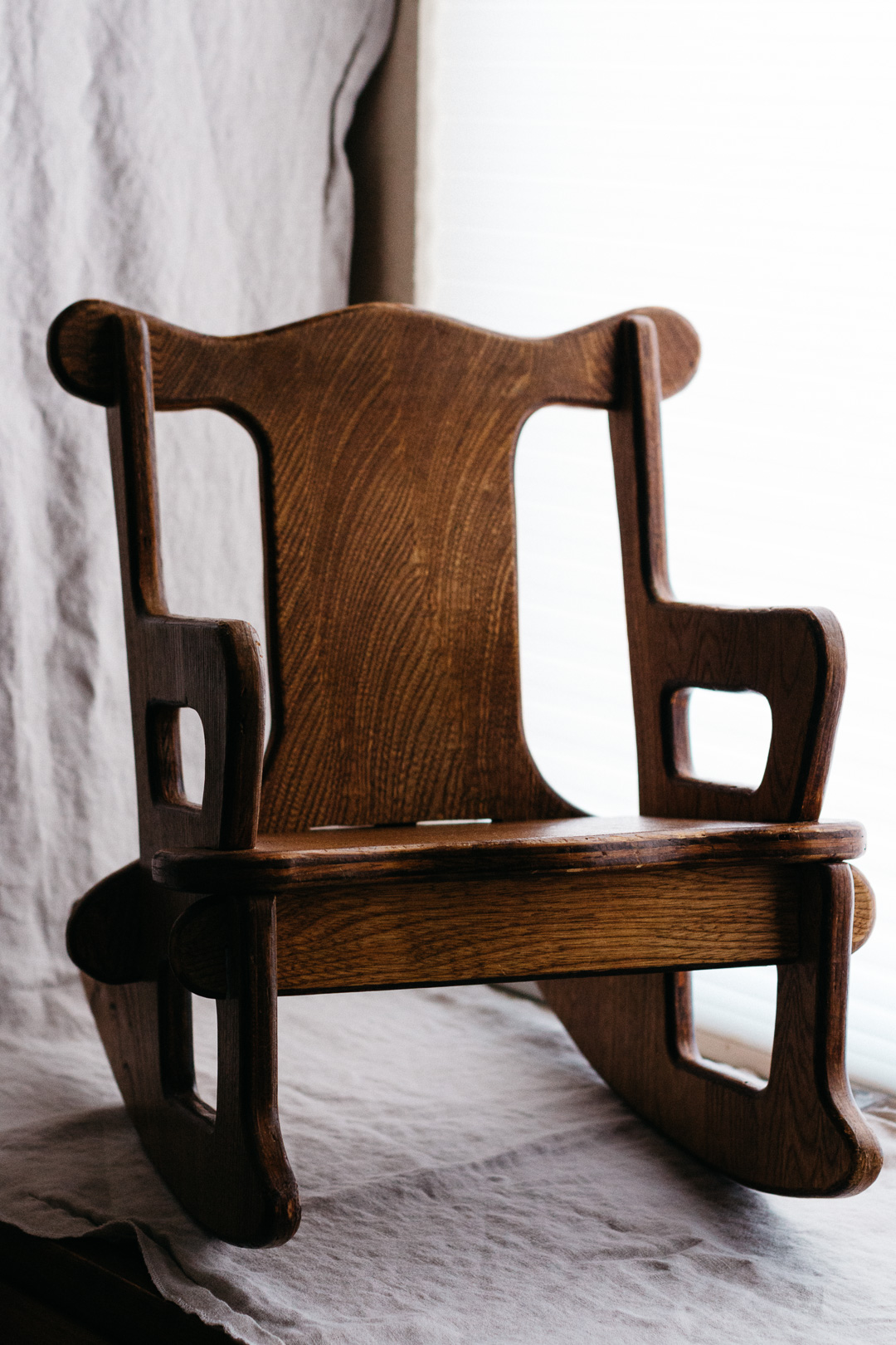 A side angle shot of a child sized wooden rocking chair.