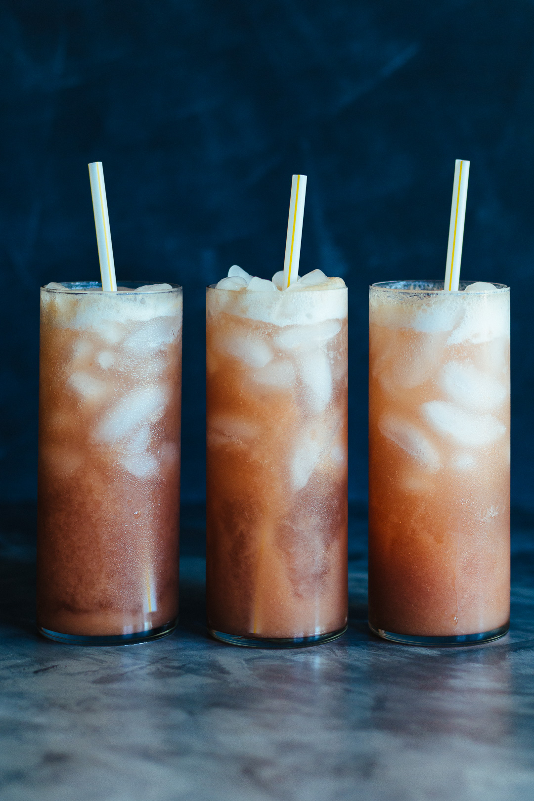 Vertical shot of three tall glasses in a line filled with Rhubarb Whiskey Collins with a straw in each.