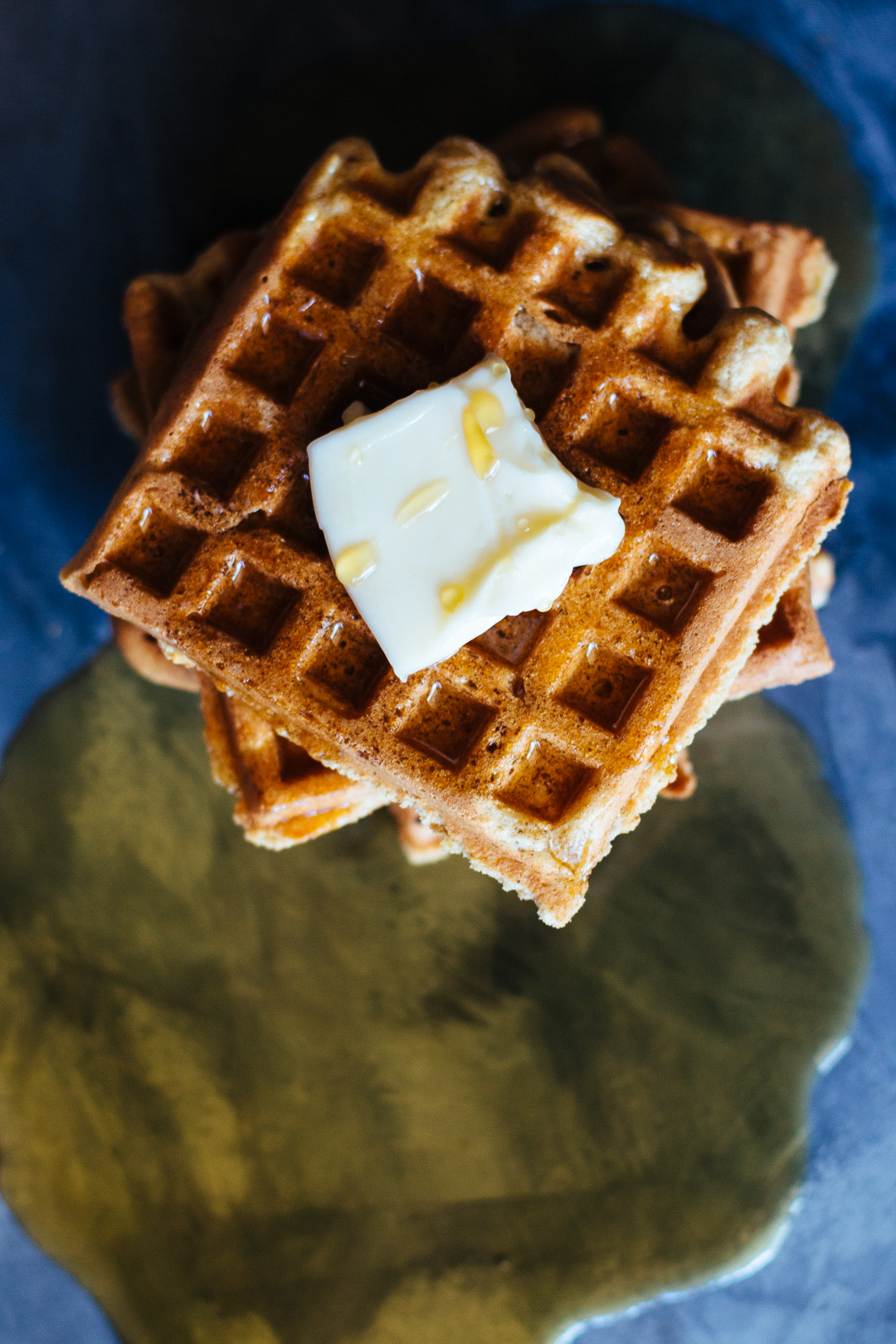 Overhead shot of a stack of waffles with a pat of butter on top and drizzled with maple syrup.