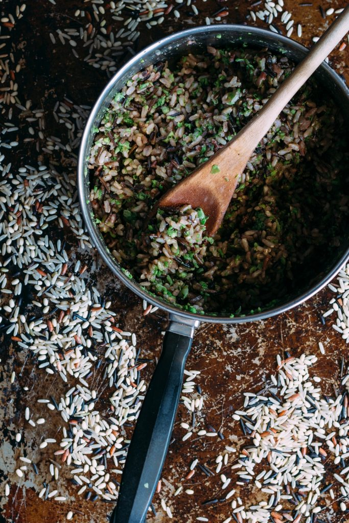 Overhead shot of saucepan with cooked wild rice and a wooden spoon on a baking sheet and dry wild rice