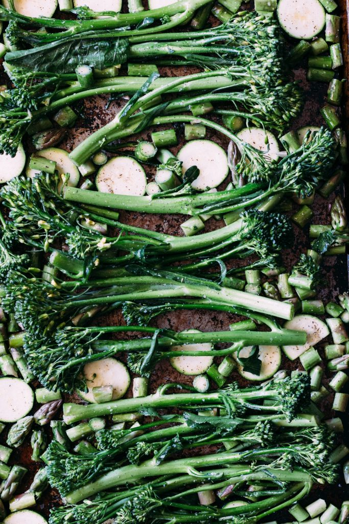 Overhead shot of raw broccolini, zucchini slices, and diced asparagus spread out on a baking sheet