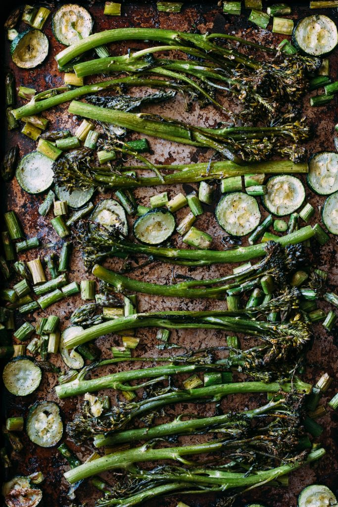 Overhead shot of oven roasted broccolini, zucchini slices, and diced asparagus spread out on a baking sheet