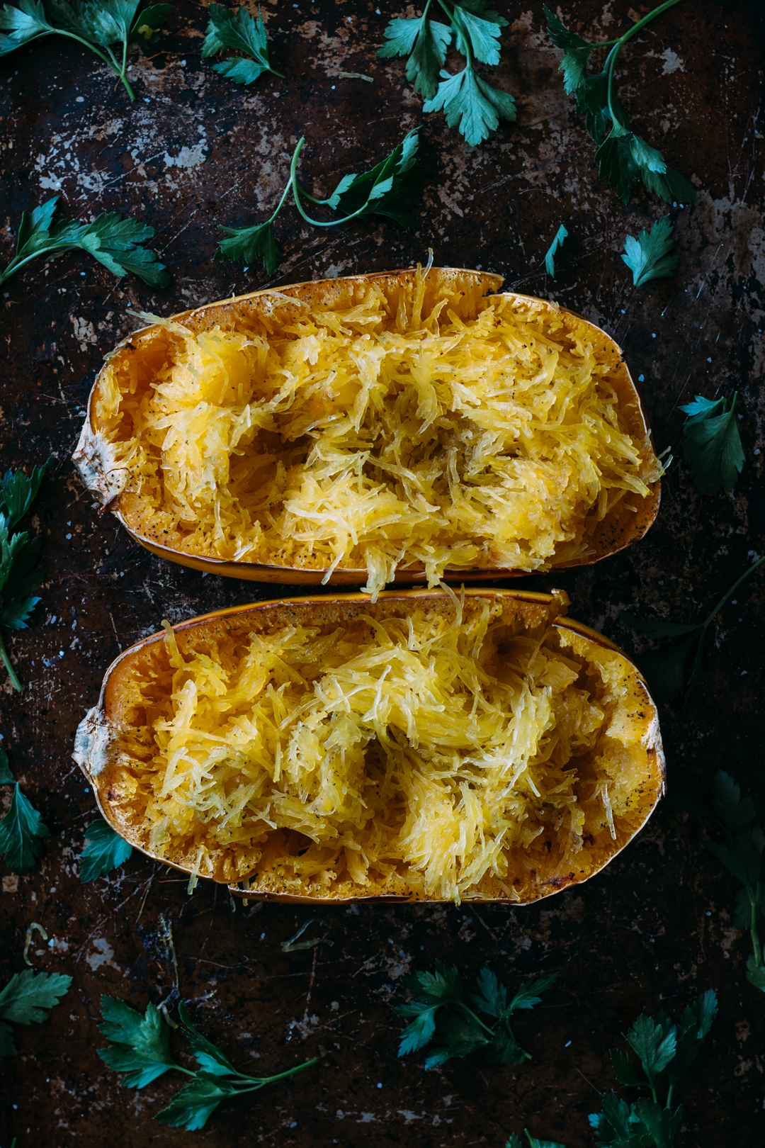 Overhead shot of two baked and tossed spaghetti squash halves on a baking sheet surrounded by parsley
