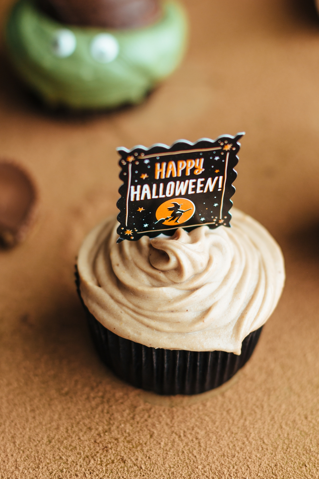 Slight overhead shot of a frosted cupcake with a happy halloween sign stuck in the top.