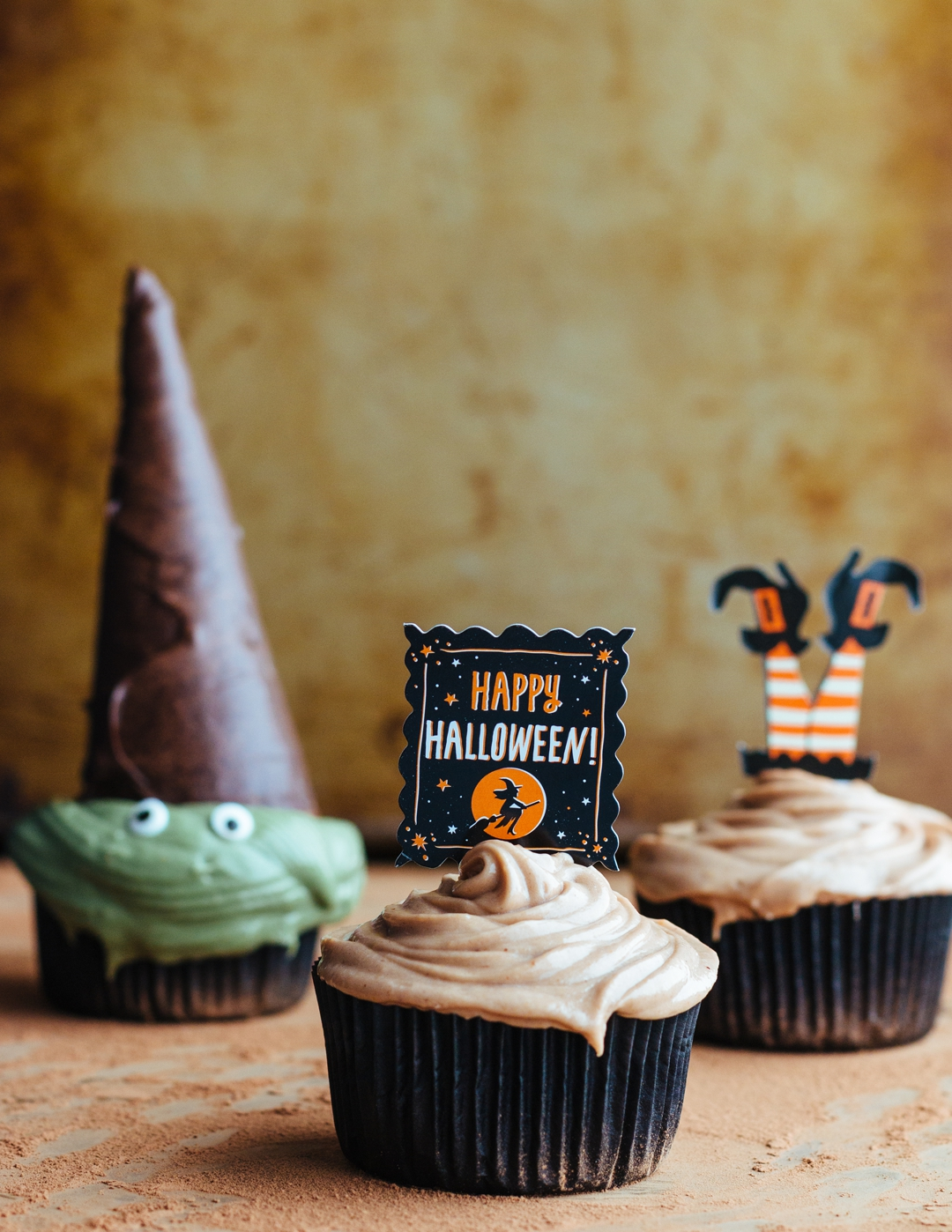 Straight on shot of three frosted cupcakes: one is decorated like a witch, another has a Happy Halloween sign stuck in it, and another has witches feet sticking out of the top.