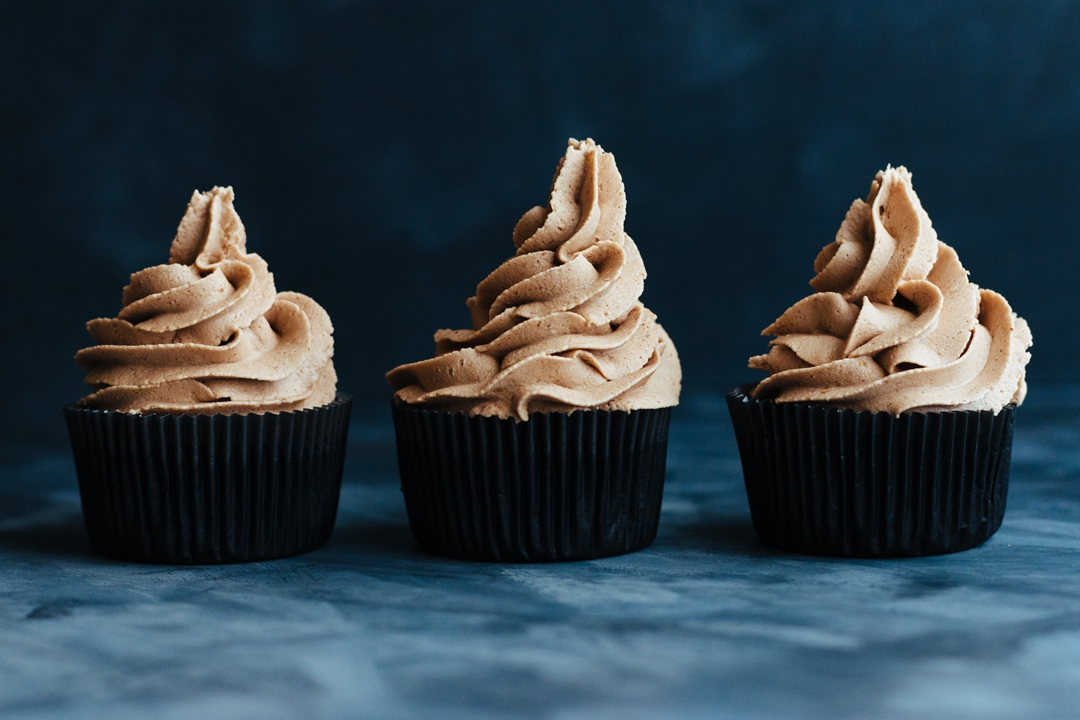 Straight on shot of three frosted Reese's Peanut Butter Cup Cupcakes lined up in a row.