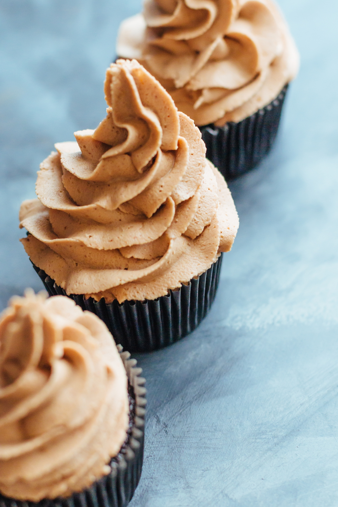 Angled vertical shot of three cupcakes topped with frosting.