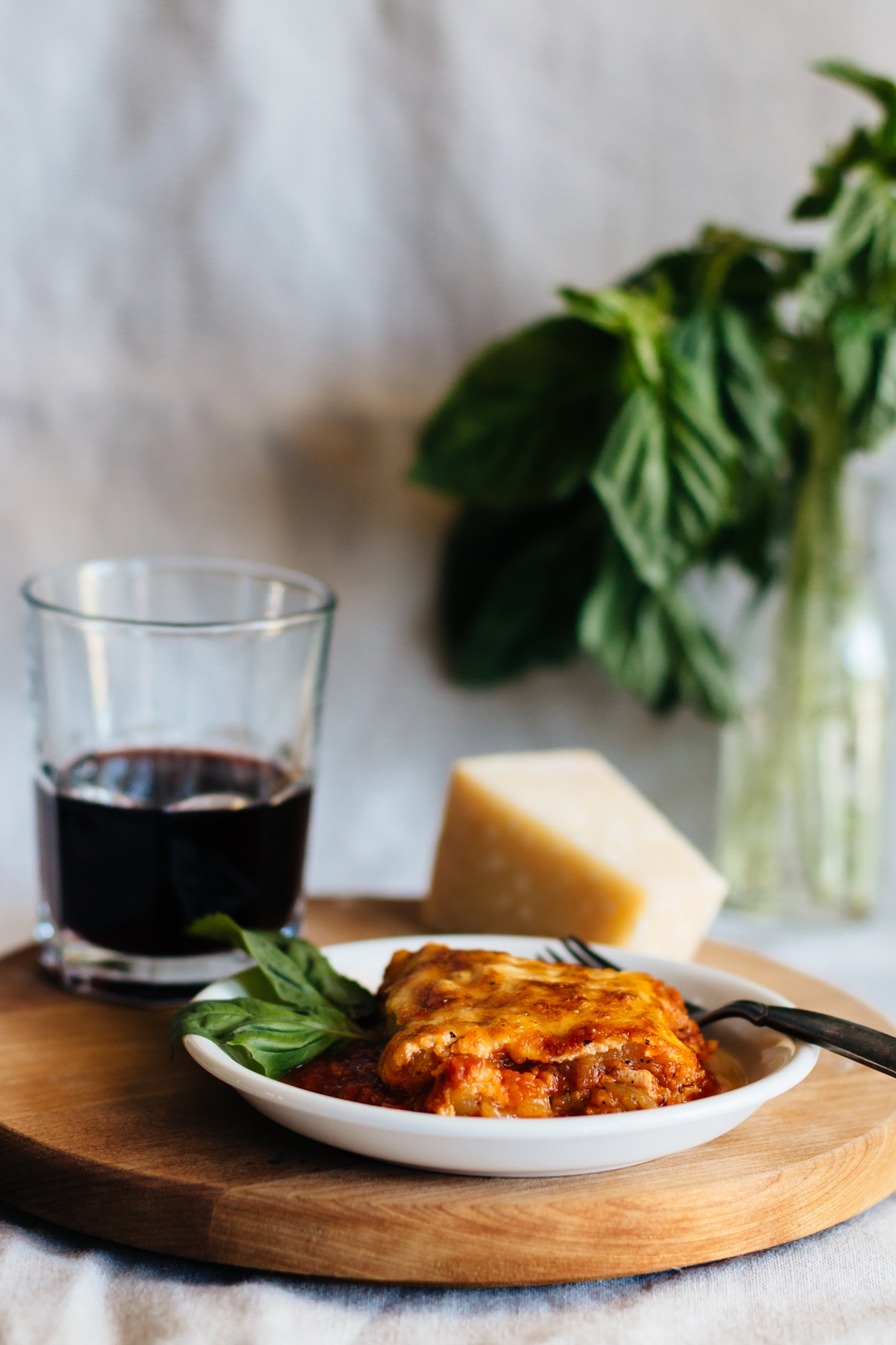 Vertical shot of a slice of zucchini lasagna on a plate with a fork surrounded by parmesan cheese and a glass of wine.