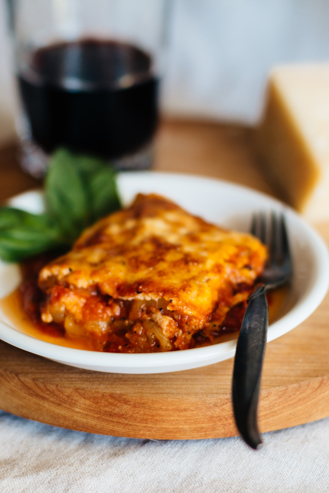 A close up vertical shot of a slice of zucchini lasagna on a plate with a fork.