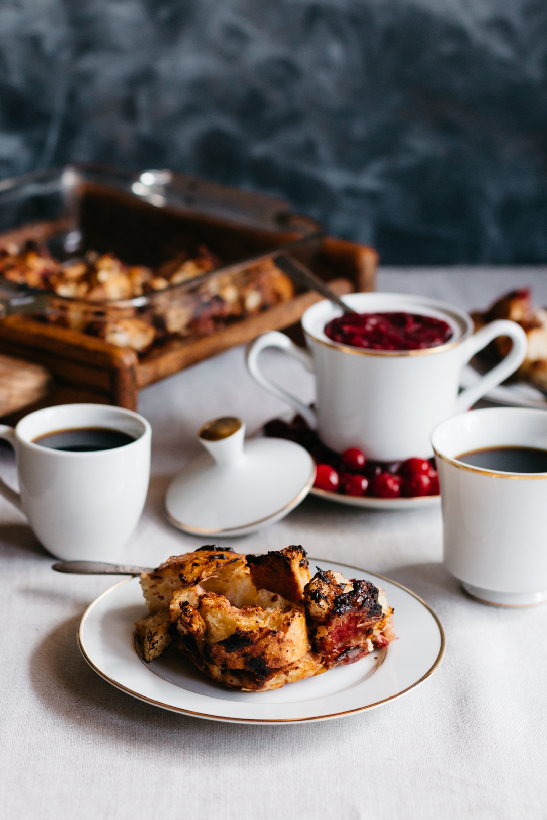 Vertical shot of a serving of savory French toast casserole on a plate with coffee cups, cranberry sauce, and the casserole in the background.