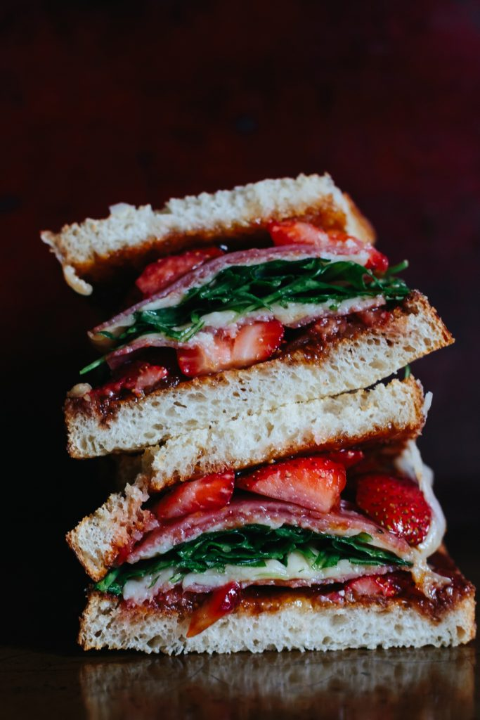 Side shot of two strawberry grilled cheese with salami, cheese, and arugula sandwich halves stacked on top of each other.