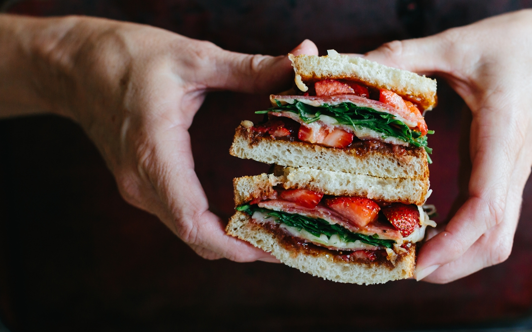 Head on shot of hands holding a strawberry grilled cheese sandwich sliced in half and stacked together.