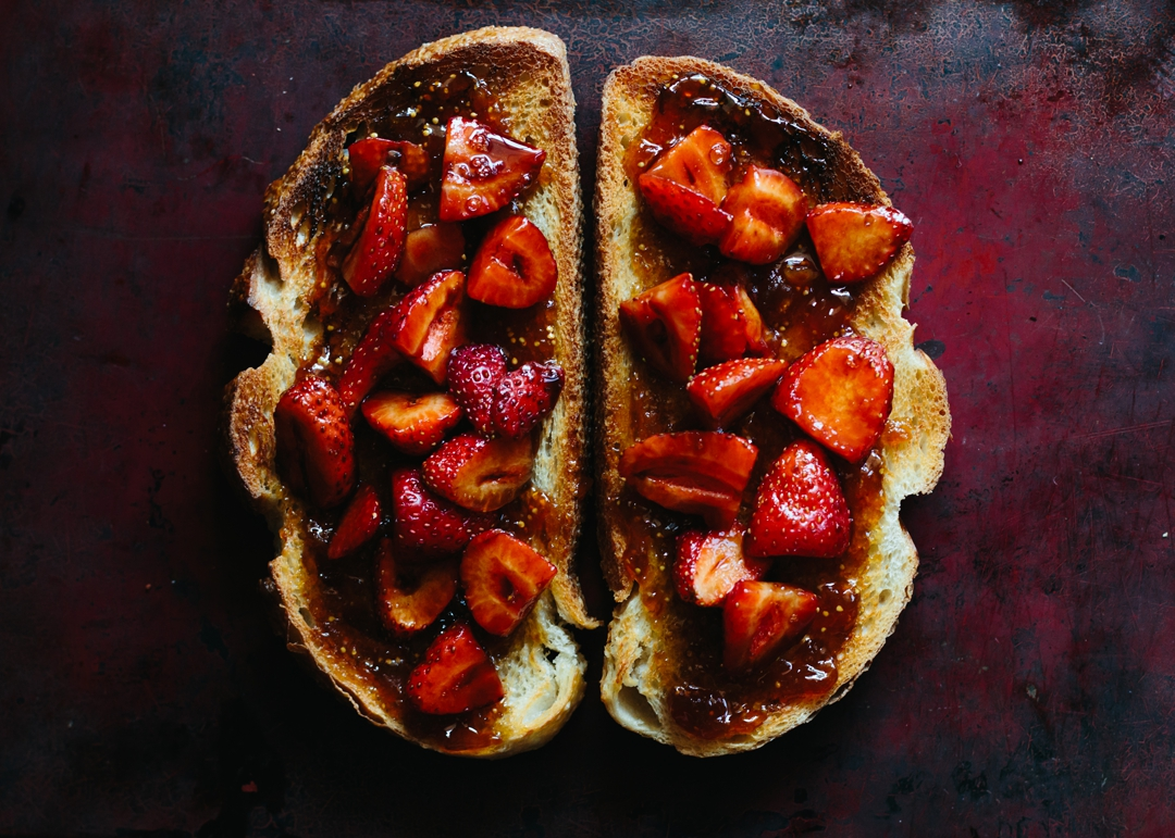 Overhead shot of two slices of toast covered in fig jam and sliced strawberries on a baking sheet