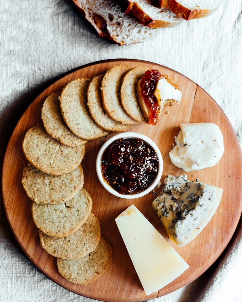 Overhead shot of pumpkin seed biscuits on round wooden cutting board with fig jam and three cheeses.
