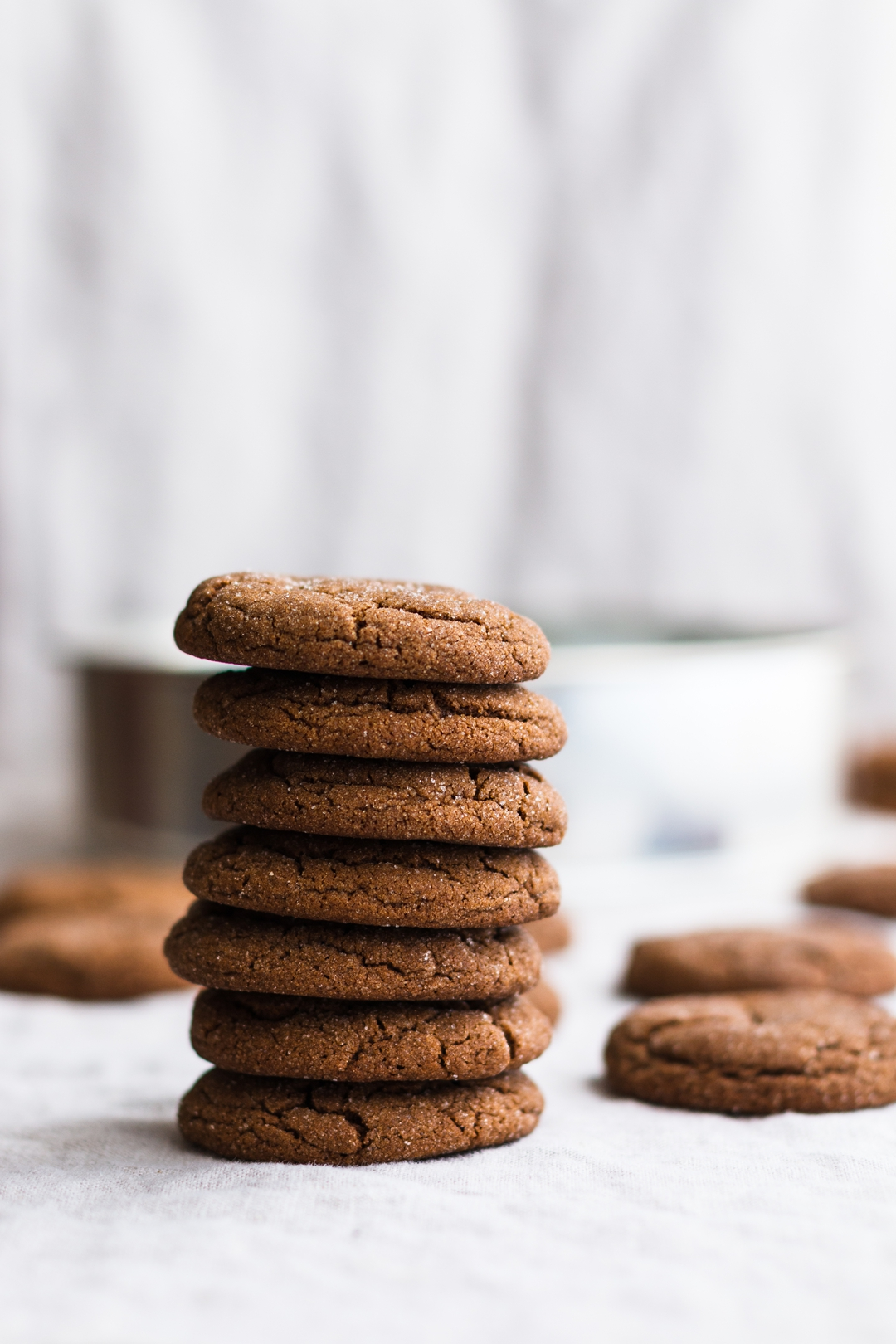 Straight on shot of stacked molasses cookies surrounded by more cookies in the background.