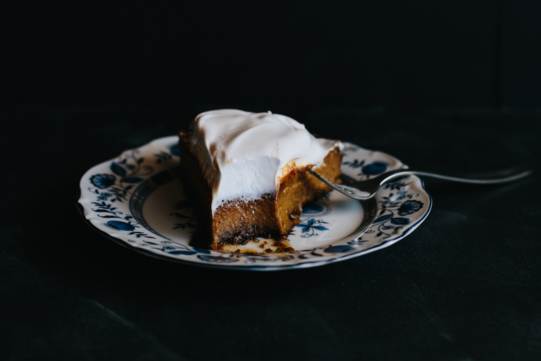 Horizontal side shot of a slice of pumpkin pie on a plate with a bite out of it.