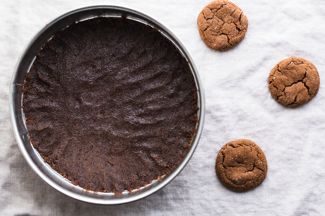 Overhead shot of the cookie crust pressed onto the bottom of a spring form pan surrounded by three molasses cookies.
