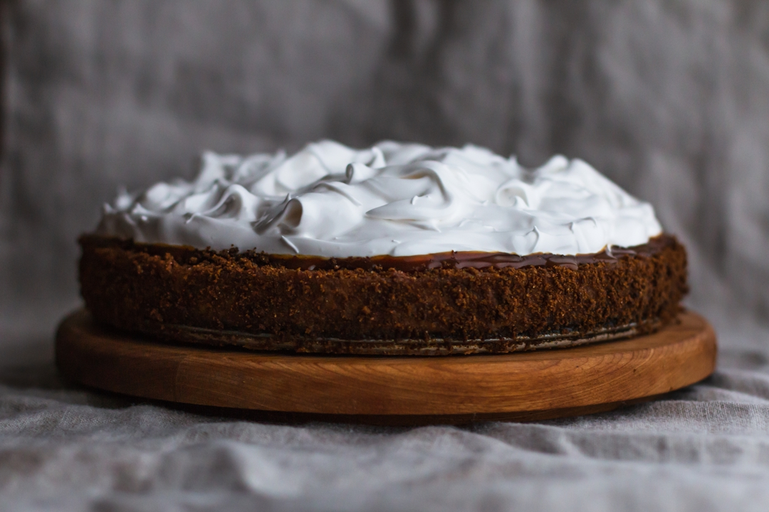 Straight on shot of pumpkin pie on a round wooden cake stand.