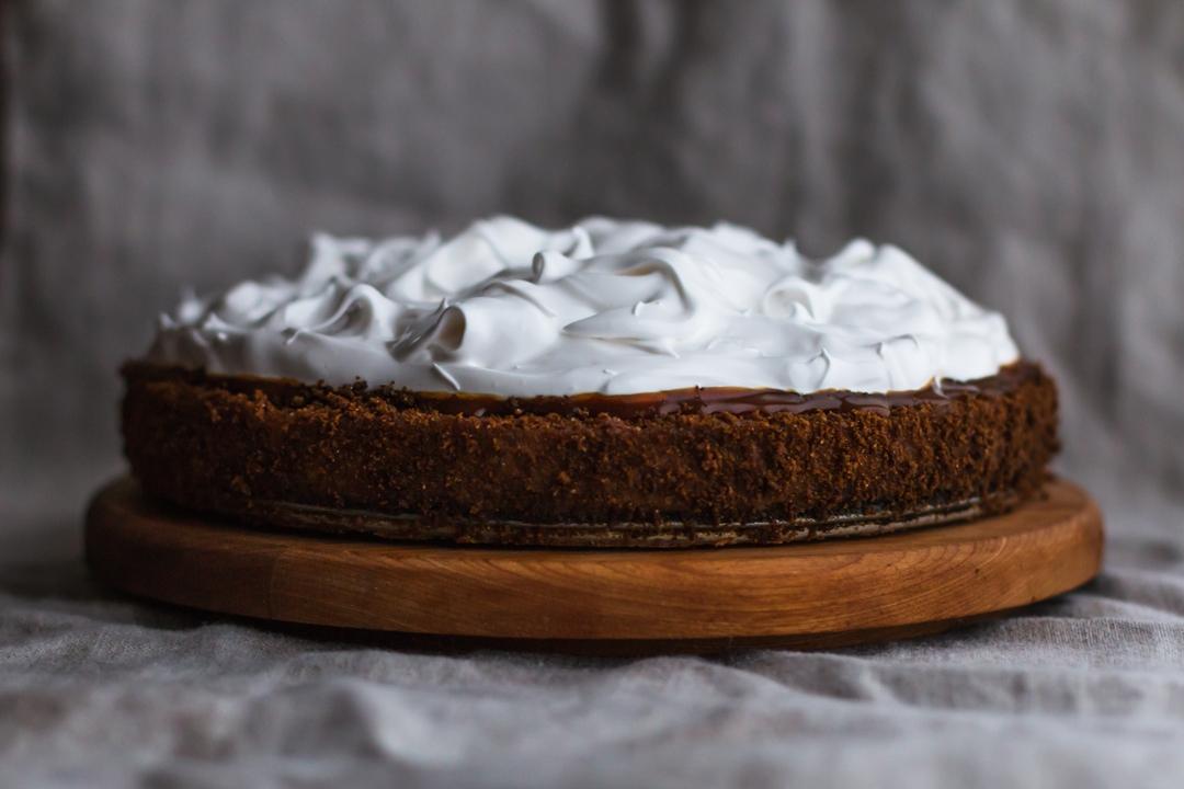 Straight on shot of pumpkin pie on a round wooden cake stand.