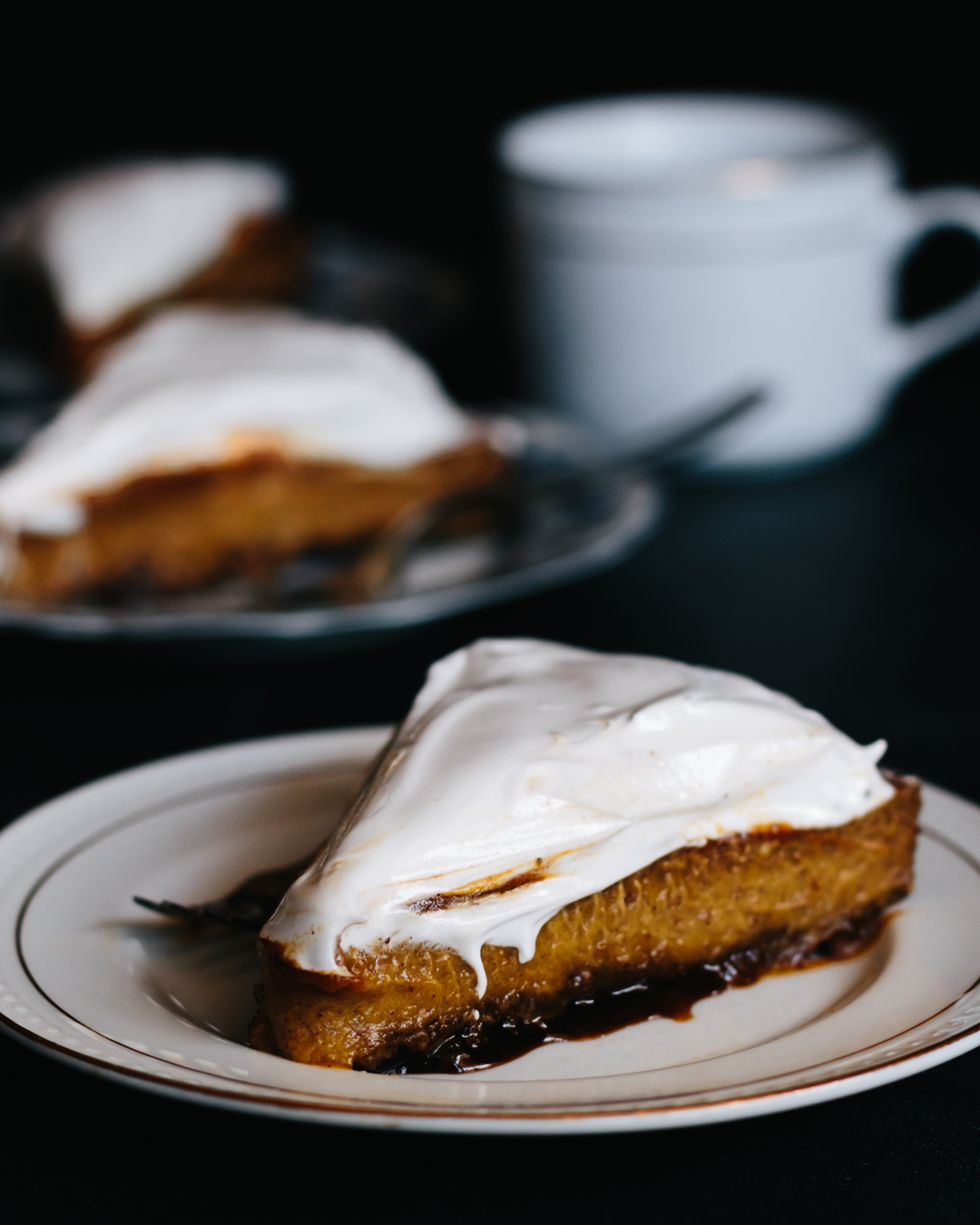 Straight on shot of a slice of pumpkin pie in front of a coffee cup and more pie.