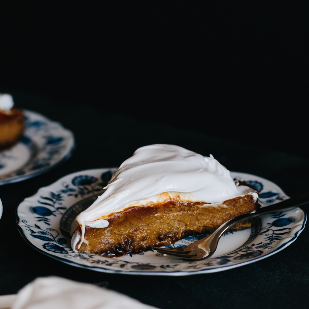 Straight on shot of a slice of pumpkin pie on a plate with a fork.