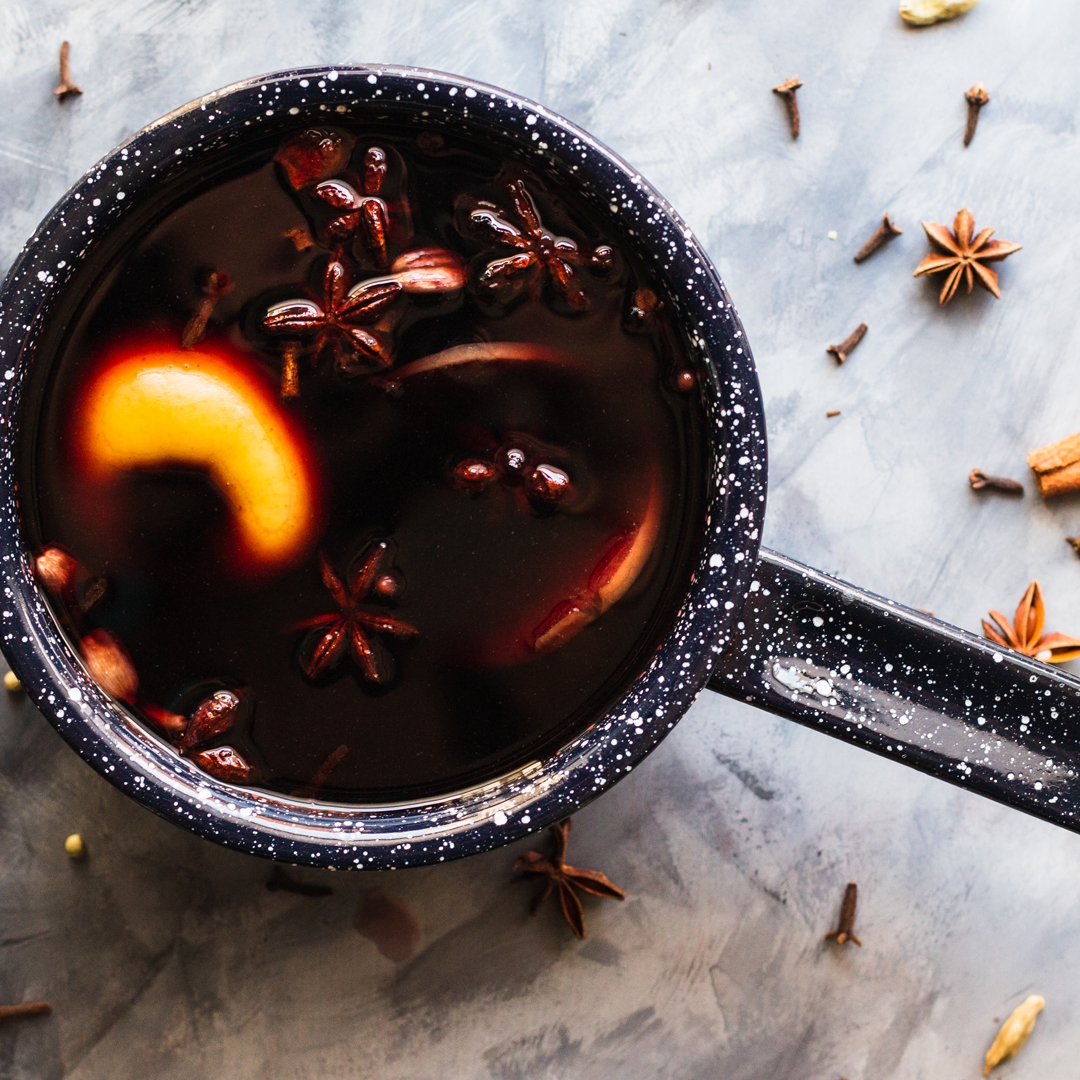 Close up overhead shot of mulled wine in a saucepan surrounded by spices.