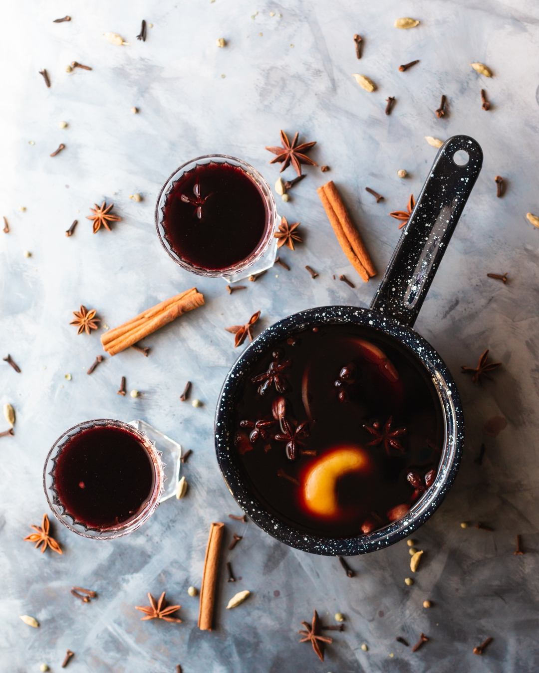 Overhead shot of saucepan filled with mulled wine surrounded by two full glasses of mulled wine and spices.