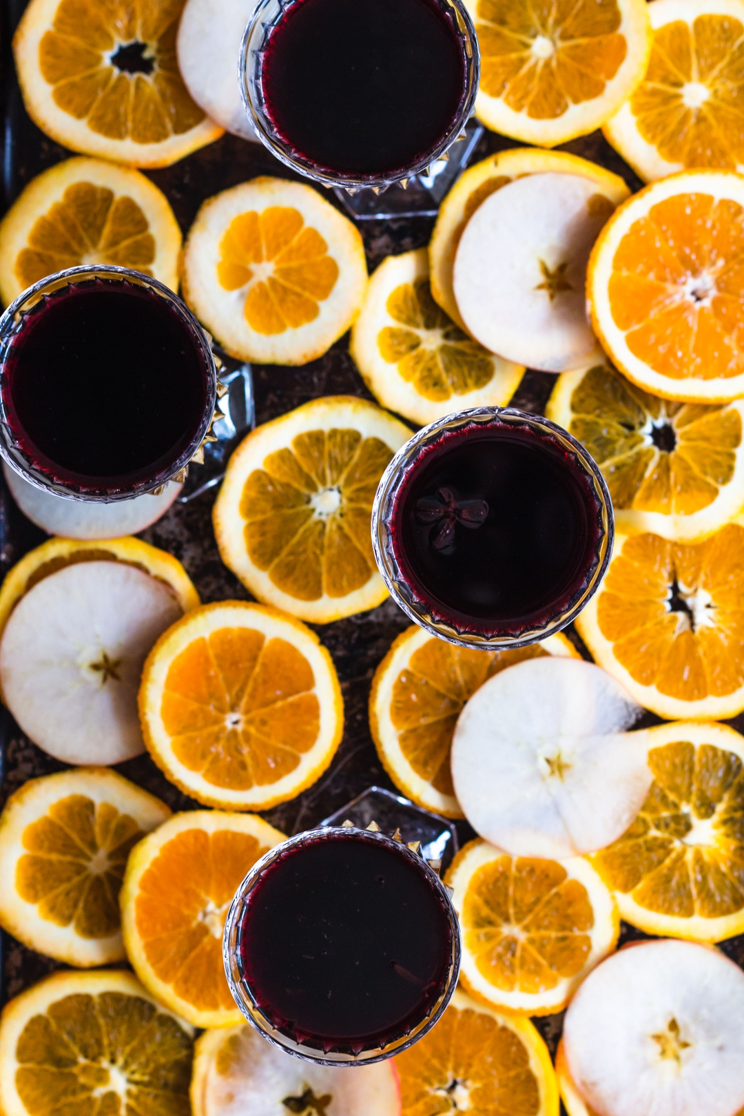 Overhead shot of four glasses filled with mulled wine surrounded by orange and apple slices.