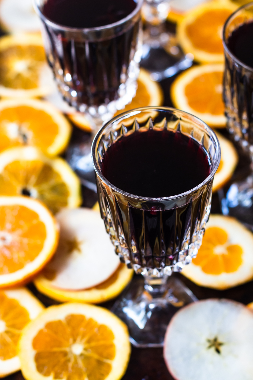 45 degree shot of glasses filled with mulled wine surrounded by sliced oranges and apples.
