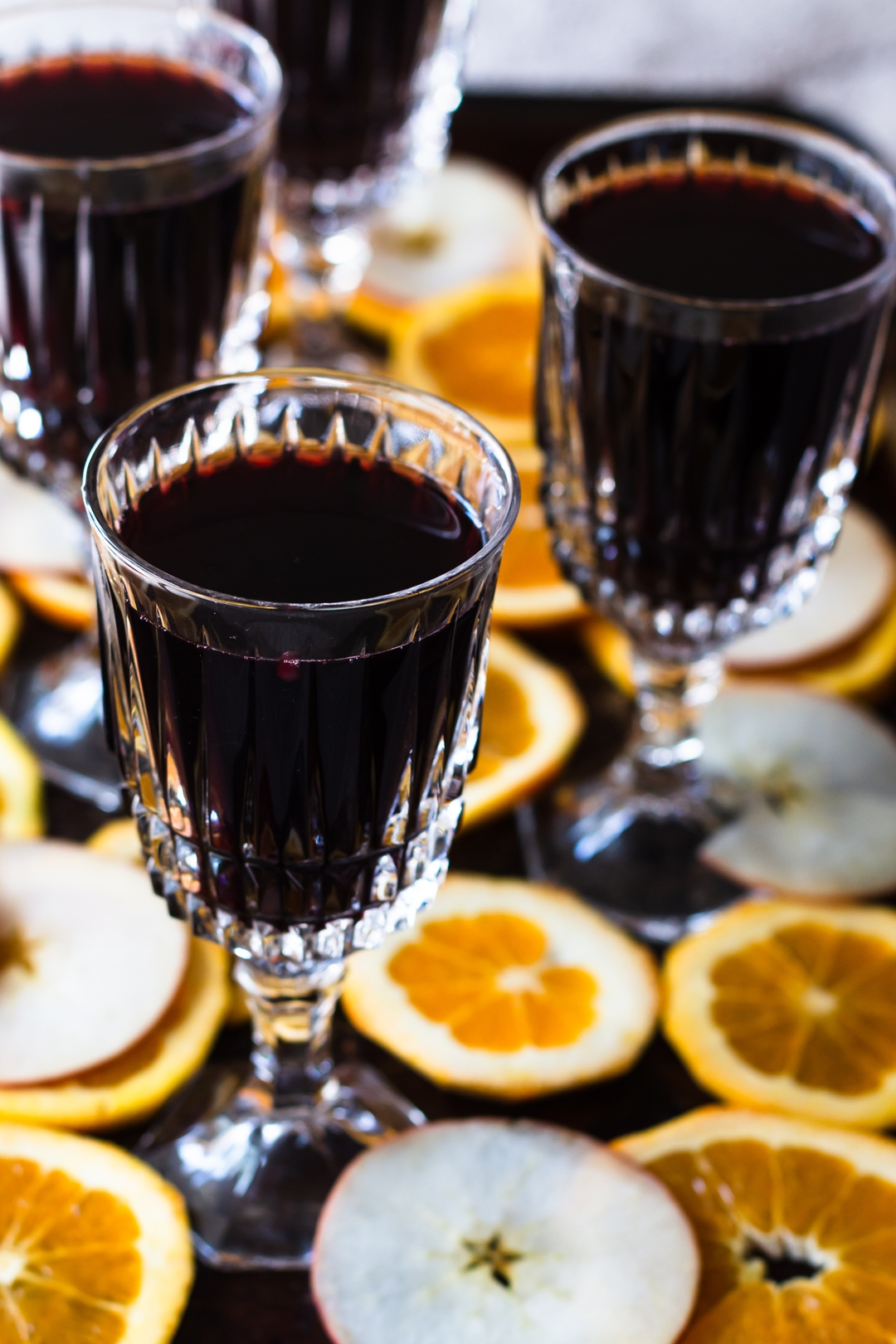 45 degree shot of mulled wine in crystal wine glasses surrounded by orange and apple slices.