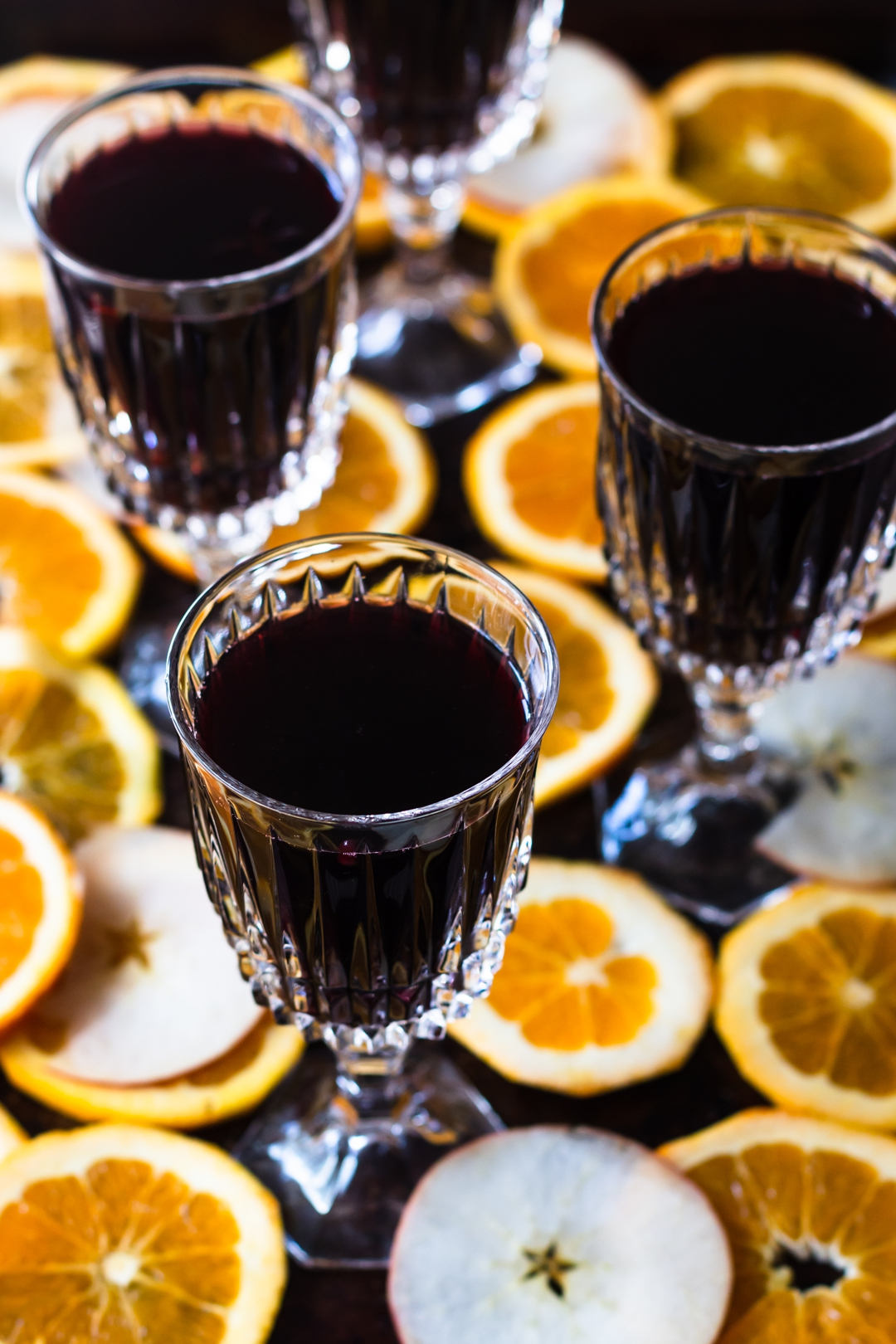 45 degree shot of mulled wine filled glasses surrounded by orange and apple slices.