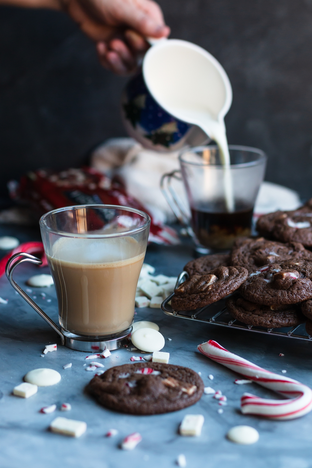 30 degree shot of a 3/4 filled latte cup, cookies, candy canes, white chocolate, and hand pouring milk into anther cup in the background.