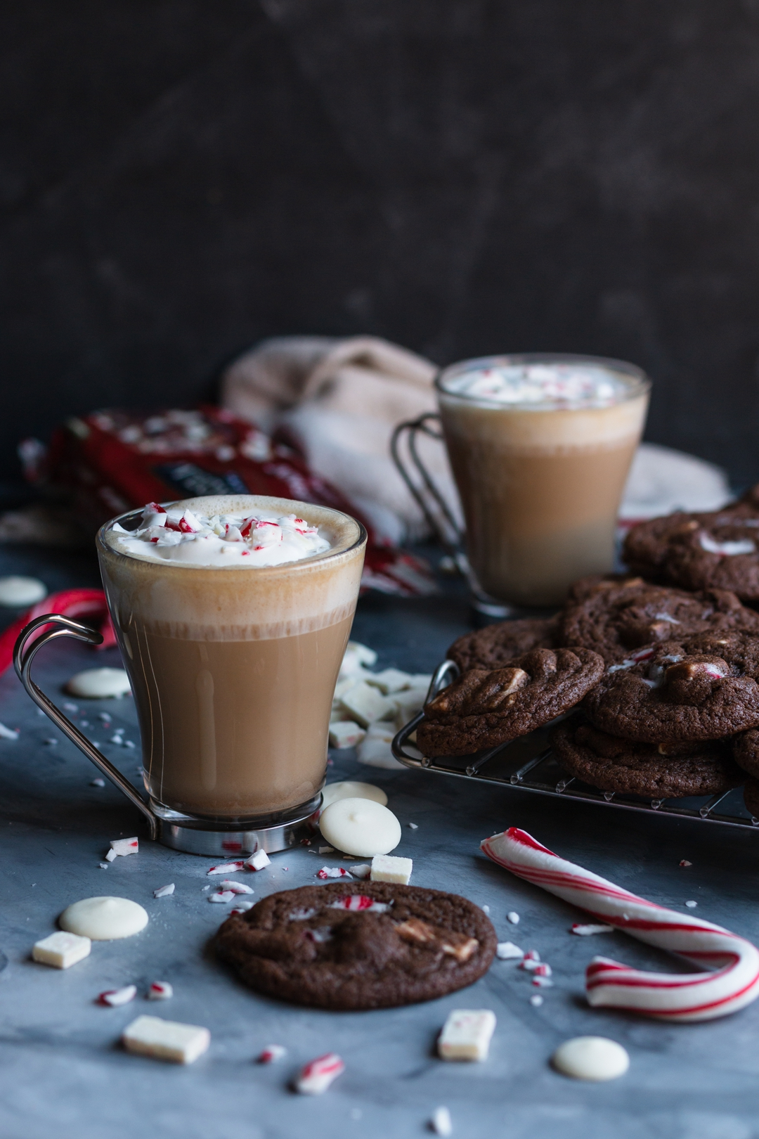 30 degree shot of latte surrounded by cookies, candy canes, white chocolate, and peppermint chips.