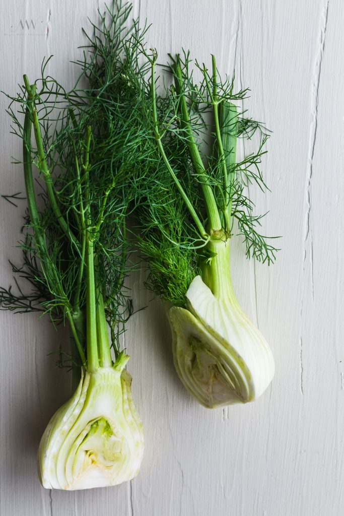 Overhead shot of fennel sliced in half on a white board