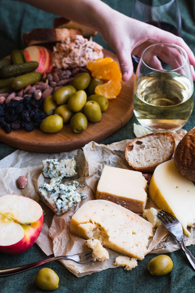Side shot of different cheeses on parchment paper surrounded by forks, olives, a halved apple, wine, and a cheese board with a hand reaching for a glass of white wine.