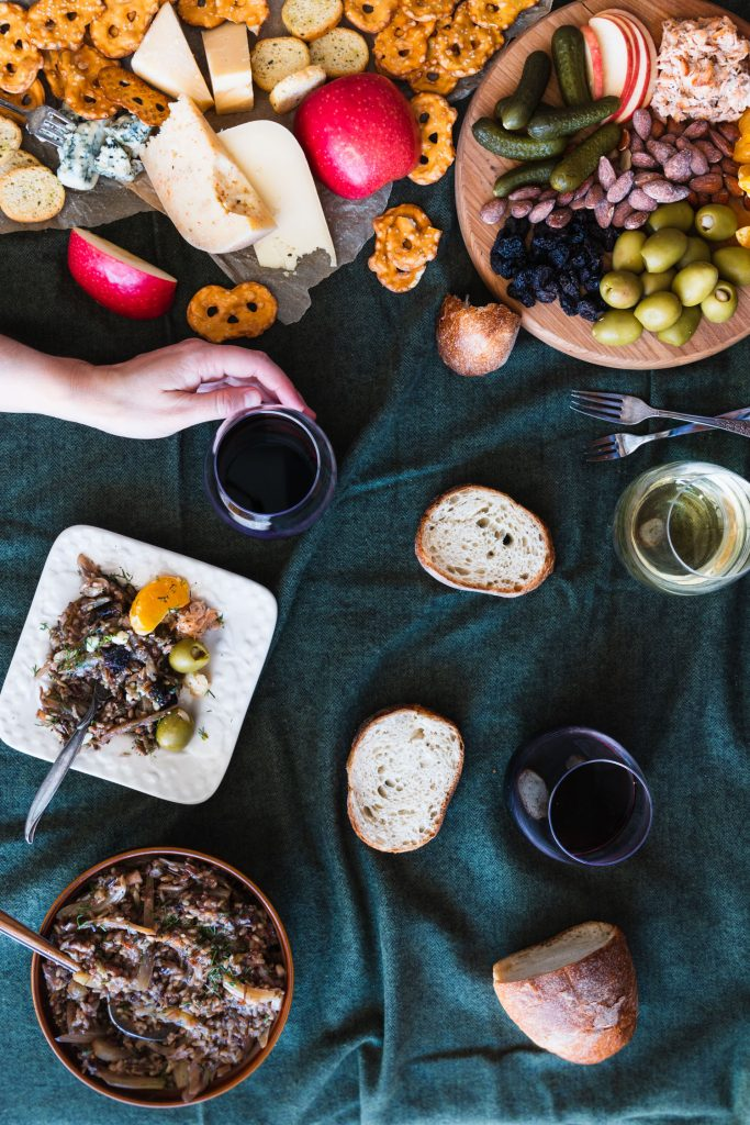 Overhead shot of picnic spread with Make Ahead Wild Rice Salad in a bowl, a plate with some salad and sides, wine glasses, bread, and cheese board with a hand reaching for a glass of wine.