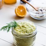 45 degree shot of lemon and dill infused sugar in a mason jar with a sprig of dill sticking out.