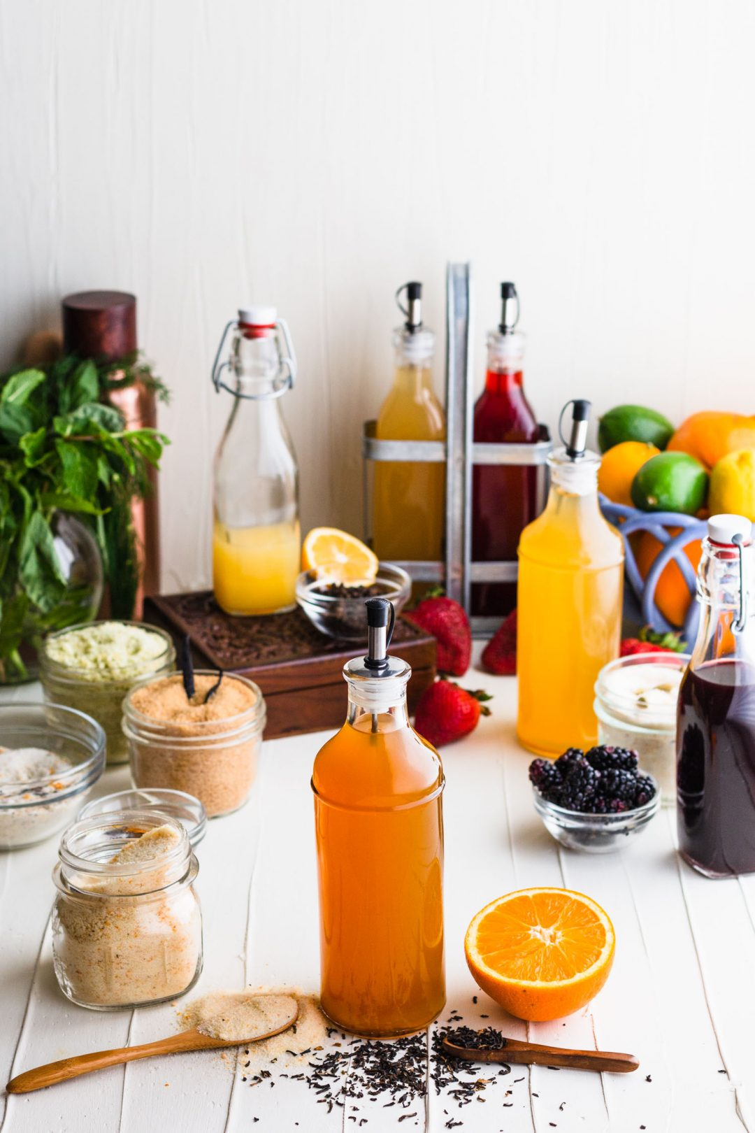Orange shrub surrounded by wooden spoons with sugar and tea, an orange half, and other shrubs and infused sugars.