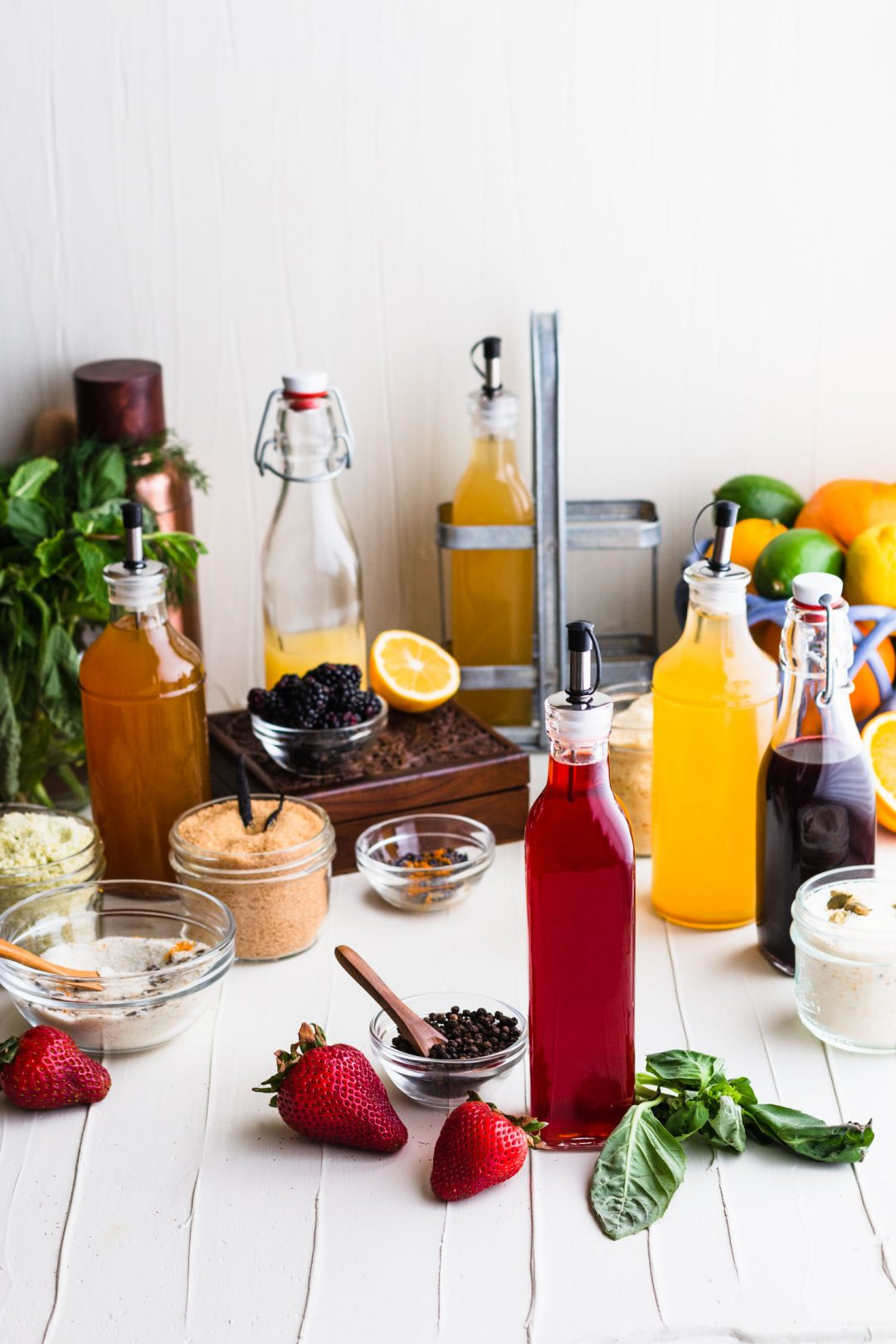 A collection of infused sugars and shrubs in mason jars and oil bottles with a strawberry shrub surrounded by strawberries, basil and peppercorns in the front.