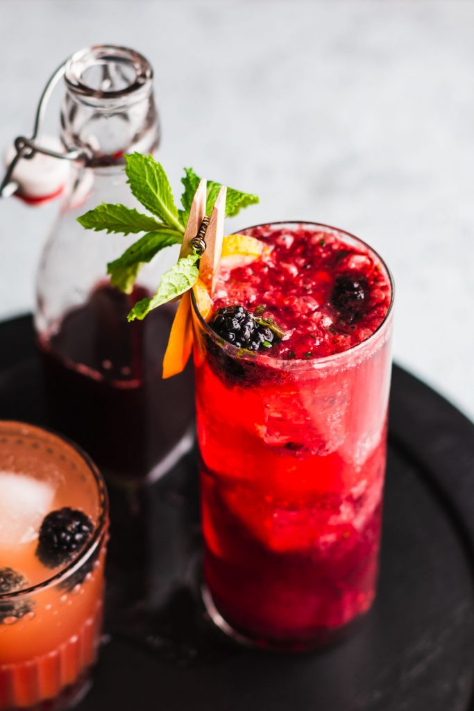 Close up 45 degree shot of Blackberry Gin Fizz in a highball glass surrounded by a bottled shrub and mocktail.