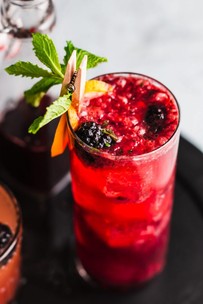 40 degree close up shot of Blackberry Gin Fizz in a highball glass on top of a black wooden serving platter.