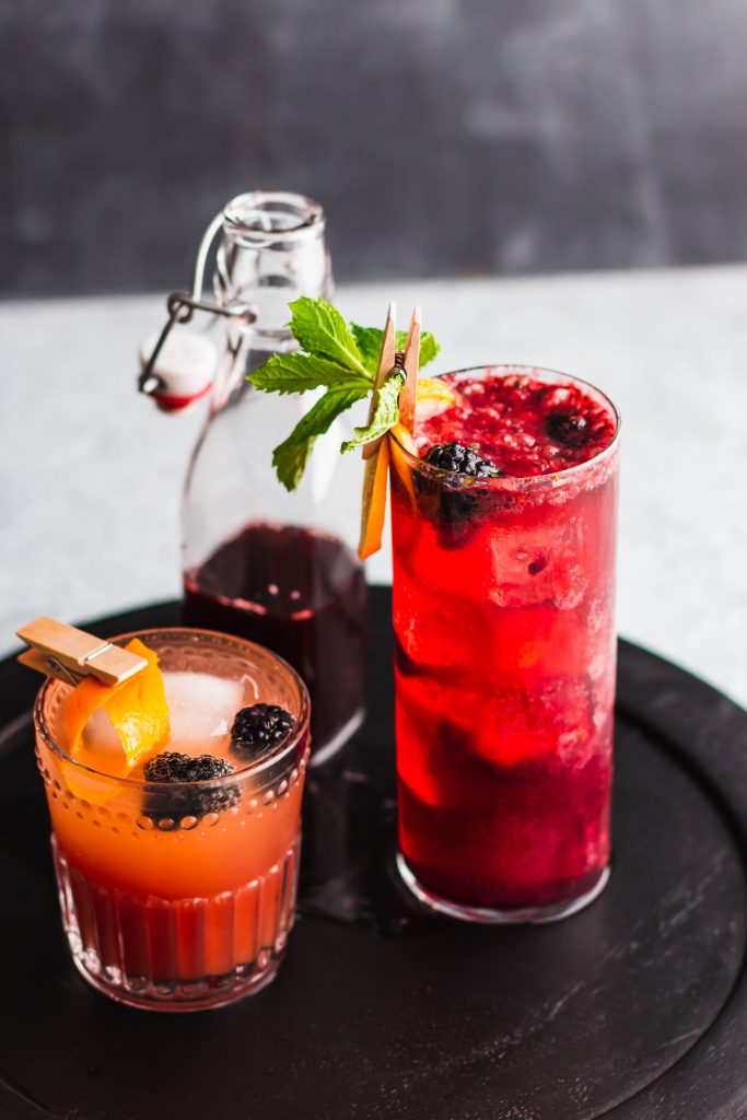 Side shot of a Blackberry Gin Fizz in a highball glass on top of a black wooden surface and surrounded by a mocktail and a bottled shrub.