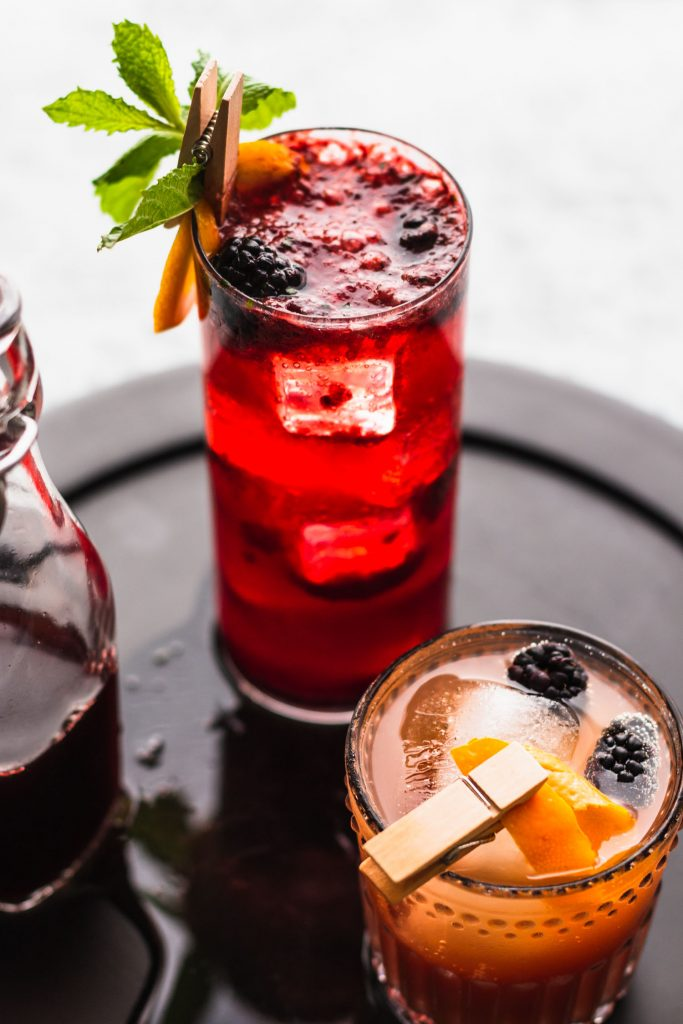 40 degree semi-close up shot of a Blackberry Gin Fizz in a tall highball glass on top of a black wooden serving plate surrounded by a mocktail and bottled shrub.
