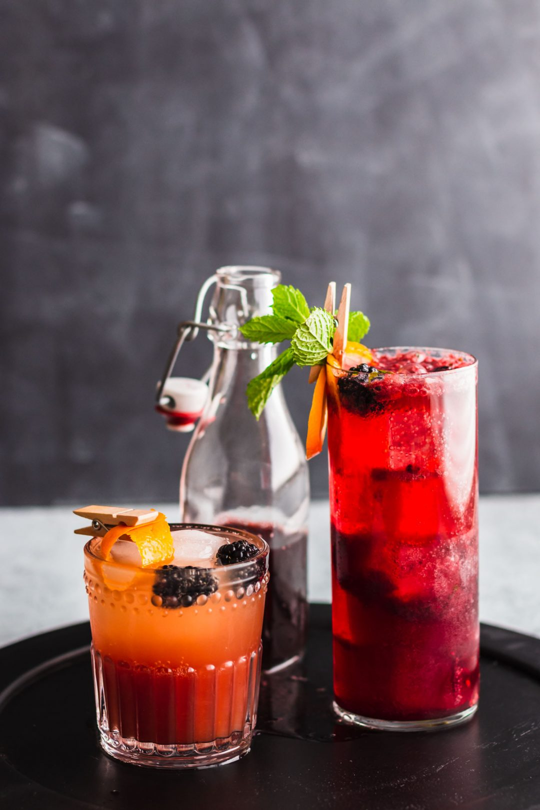 Vertical side shot of Blackberry Gin Fizz in a highball glass next to a short mocktail on a black wooden plate in front of a bottled blackberry shrub.