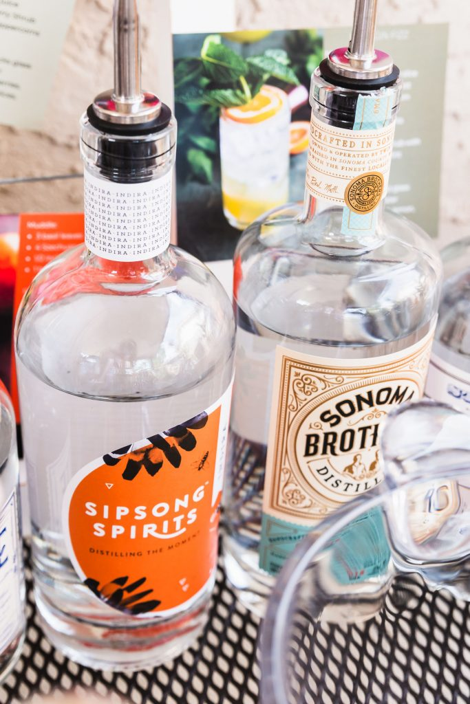 Vertical shot of a bottle of Indira Gin from Sipsong Spirits surrounded by other bottles of gin.