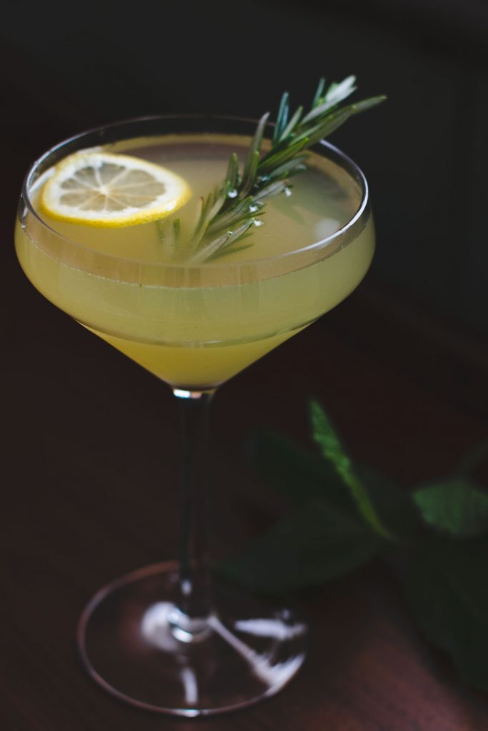 Close up side shot of neat version of a Gin Lemonade Cocktail in a coupe glass with a lemon slice and rosemary spring garnish.