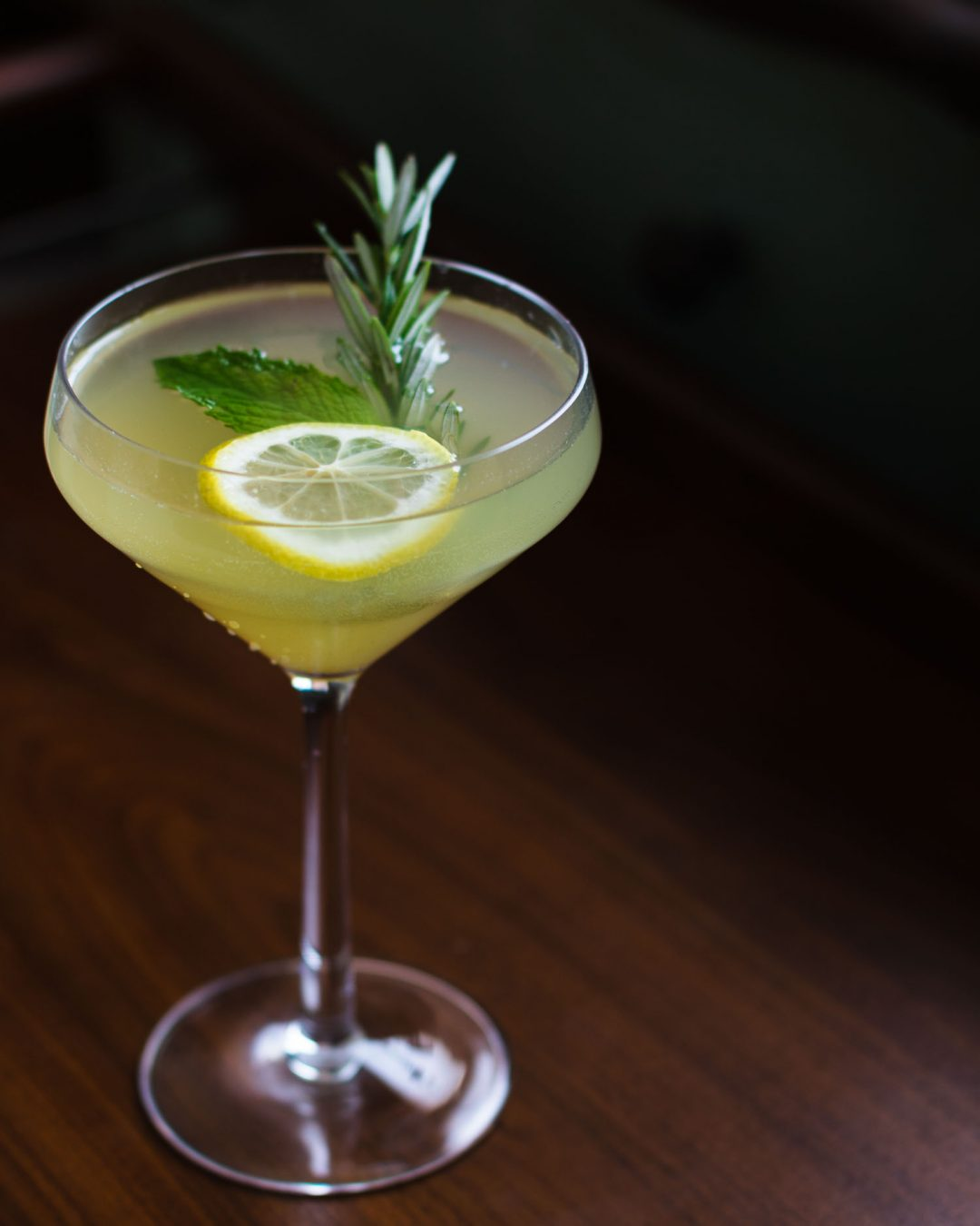 Side shot of a Gin Lemonade Cocktail served neat in a coupe glass with a slice of lemon, rosemary, and mint.